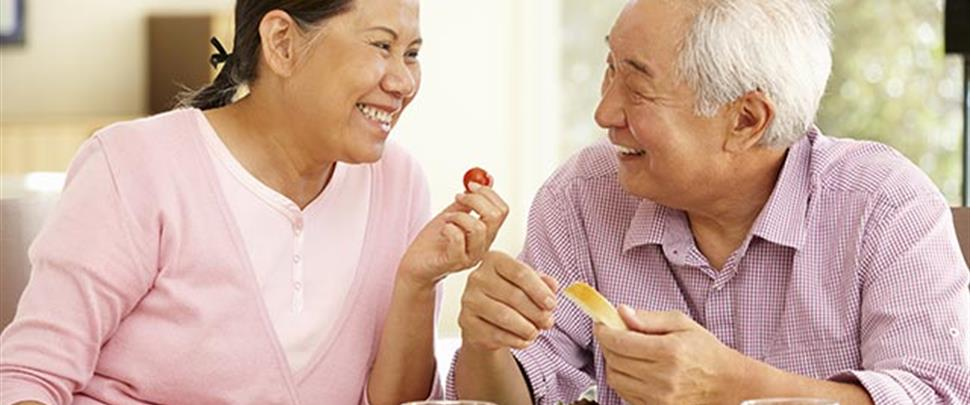 senior-asian-couple-sharing-meal-at-home